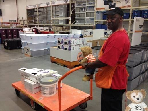 Duffy the Disney Bear helps push orange cart at Home Depot