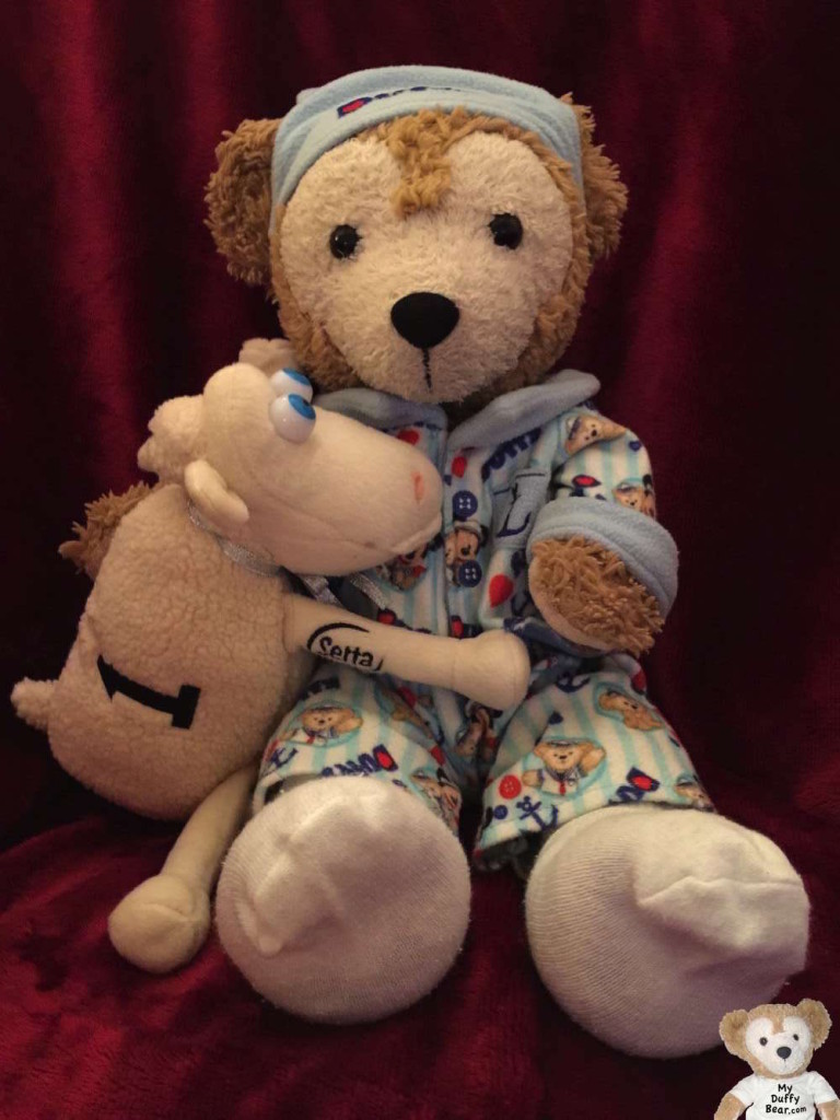 Duffy the Disney Bear snuggles with his Serta Sheep in his pajama outfit.