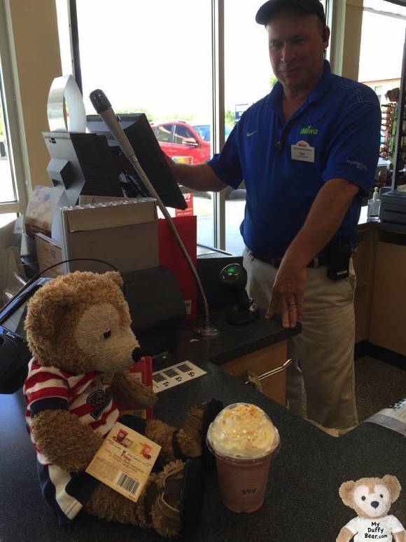 Duffy the Disney Bear hands his free smoothie coupon to the manager at the register